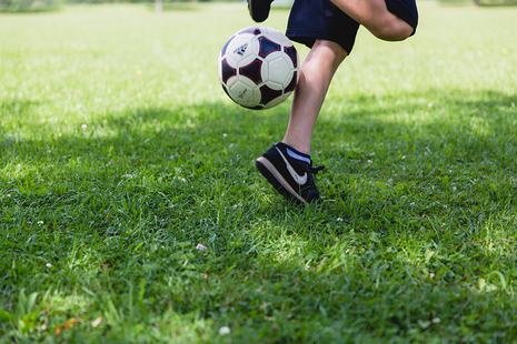 Young person kicking a football