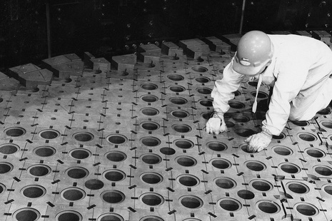 A man kneeling by some graphite blocks