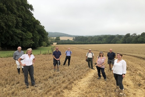 A group of people are seen standing in a field with trees and rolling hills in the background. The people are all 2m apart from one another.