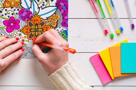Hands of a person colouring in a mental wellbeing colouring book with a pen