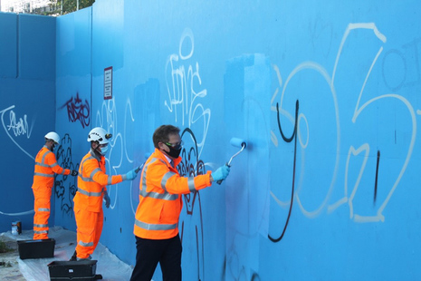 Image of workers removing graffiti