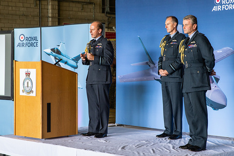 Image depicts Air Chief Marshal Mike Wigston with two deputies in uniform on a stage.
