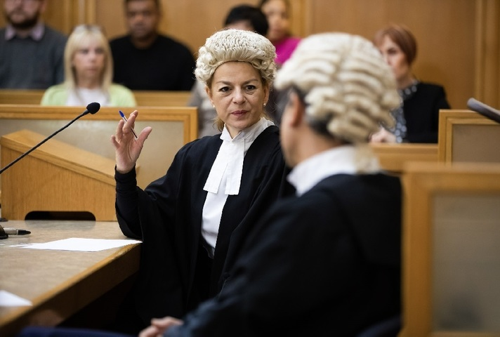 Female barrister conferring with colleague in courtroom