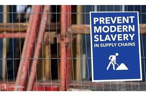 """Sign on a fence reading """"Prevent modern slavery in supply chains"""""""