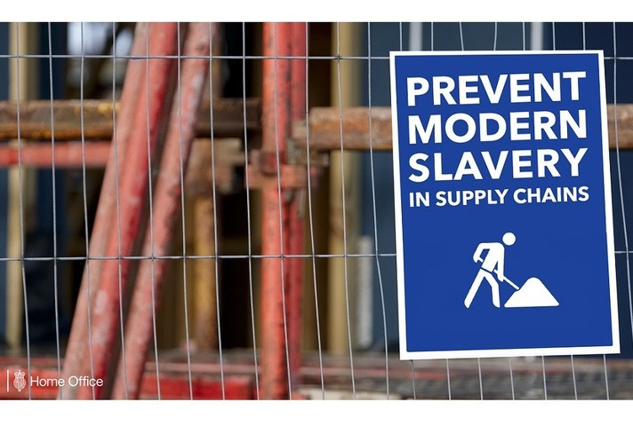 "Sign on a fence reading ""Prevent modern slavery in supply chains"""