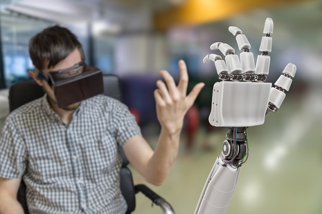 Person uses virtual reality headset and haptic technology to control robot arm in remote location