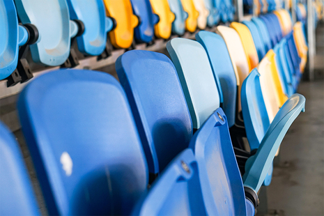 Image of multicoloured seats in sports stadium