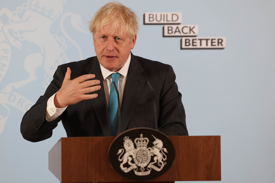 "PM Boris Johnson delivering a speech in front of a banner that reads ""Build Back Better"""