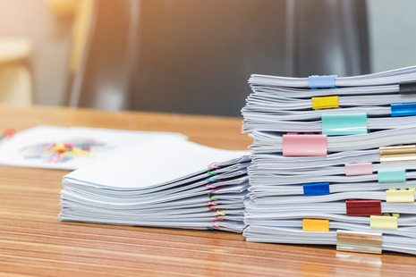 A pile of exam papers on a desk