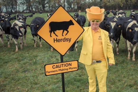 Herdsy - Founder Richard Hobson in a field with cows wearing a yellow suit and Herdsy's sign saying Caution - Farmers Making Money