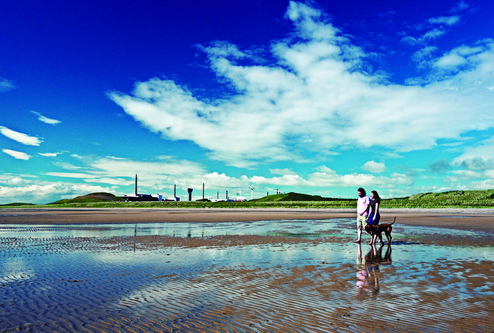 Family walking on a beach with Sellafield - in Copeland - in the background