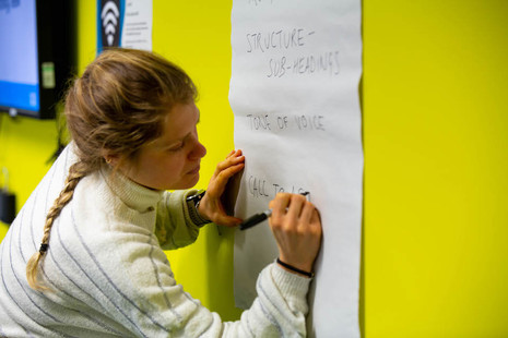 A woman writes 'tone of voice', 'structure - sub headings' and 'call to action' on a board during a content planning session.