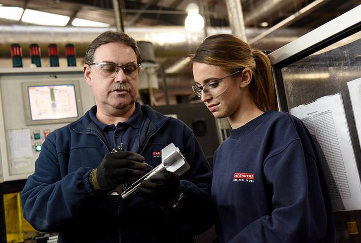 A man and a woman look at a shell they are working on.