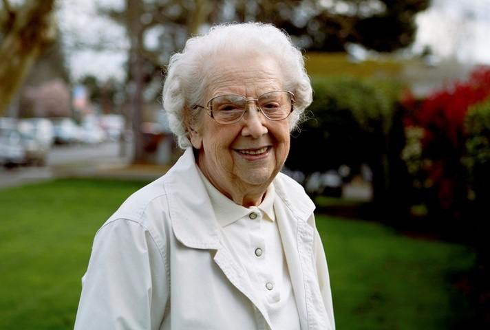 An elderly woman outdoors, smiling.