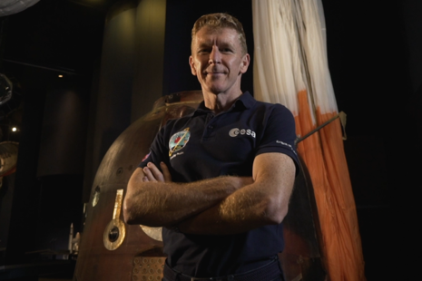 Astronaut Tim Peake stands in front of his Soyuz space capsule