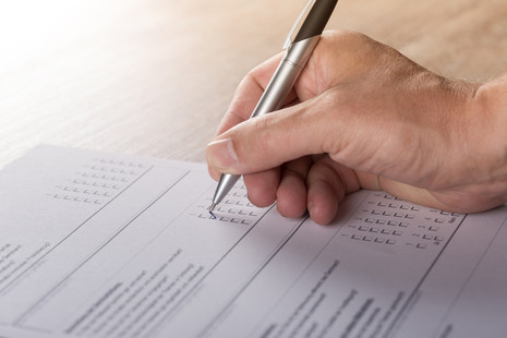 Hand with a pen filling out a survey