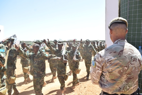 Somali soldiers march past a UK instructor during their training graduation ceremony