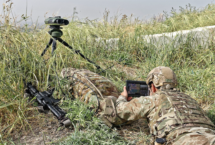 Soldier using the system, laying flat on the ground in long grass, looking into a tablet screen.