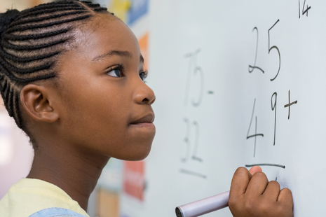 young girl solving a maths problem