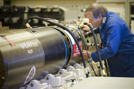 Image depicts a man working on a Spearfish torpedo.