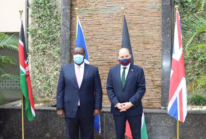 Defence Secretary Defence Ben Wallace stands alongside Dr Fred Matiang'i, Kenyan Cabinet Secretary for the Interior, in front of Kenyan and British flags