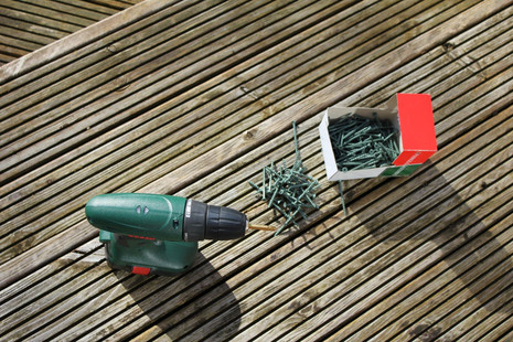 Power drill and screws on wooden decking