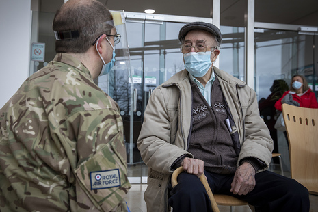 Image depicts a soldier sitting and speaking with an elderly gentleman.