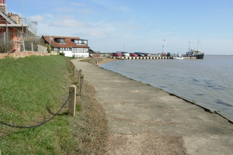 Image shows path curving from right next to the harbour past some houses towards a jetty with a boat moored at the end.