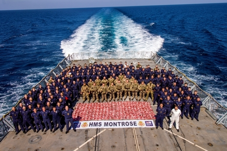 Dozens of Royal Marines and sailors stand around red bags of confiscated drugs on the deck of HMS Montrose