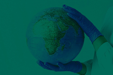 gloved hands holding a globe