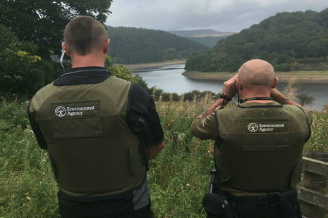 2 fisheries enforcement officers on a river bank - one using binoculars