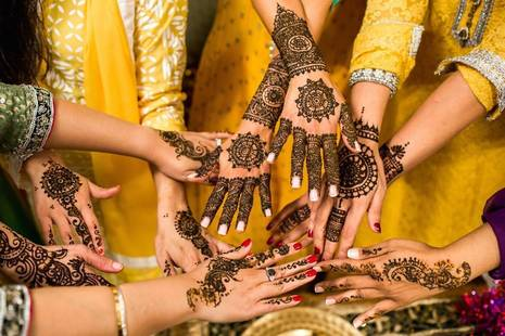 Hands decorated with henna come together in a circle