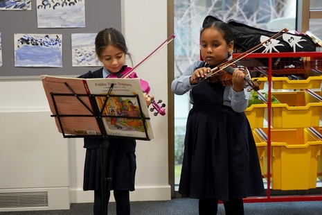 young children playing the violin