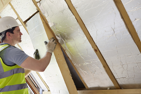 Man fitting loft insulation in a roof