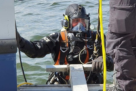 Diver emerging from water and climbing onto boat