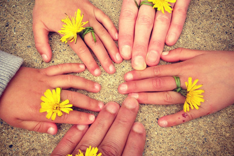 Circle of hands with dandelions on their fingers