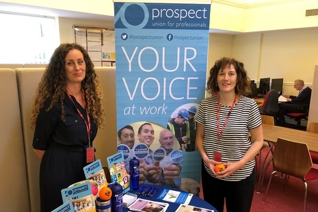 Two Prospect trade union officials standing in front of a union banner with leaflets on table