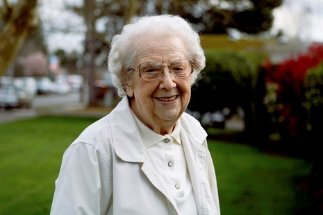 Elderly woman standing outdoors smiling