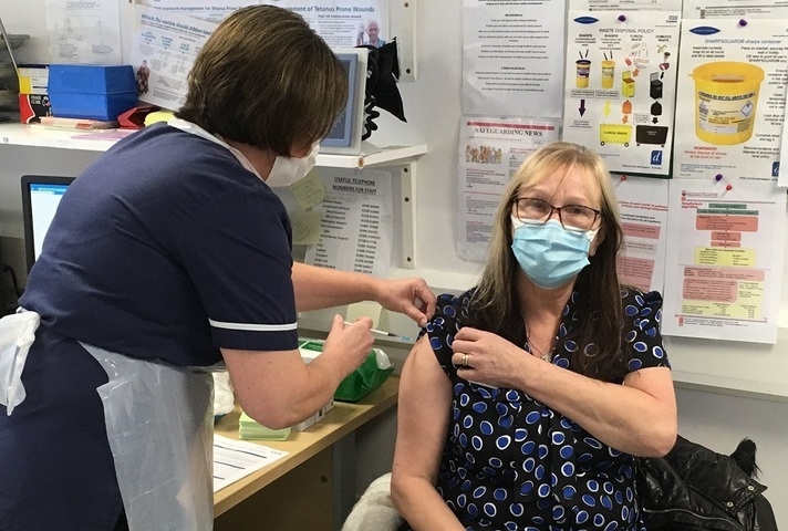 Woman being vaccinated with needle in arm