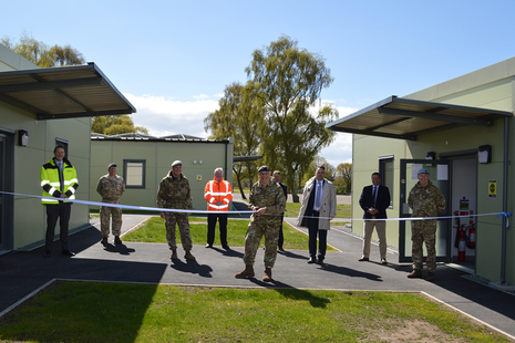 9 men stand between 2 new military buildings that are joined together by a ribbon. Lt Gen Richard Nugee cuts the centre of the ribbon.