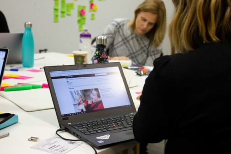 Two people sit at a laptop surrounded by post-it notes during a user research session.