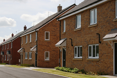 A row of new semi-detached brick houses with small front lawns.