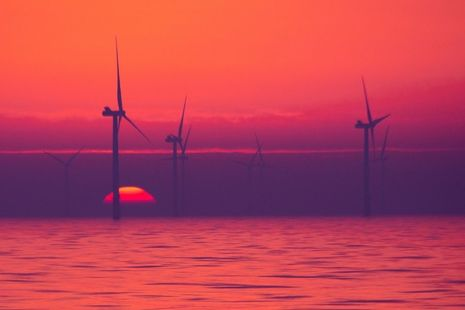 An offshore wind farm at sunset