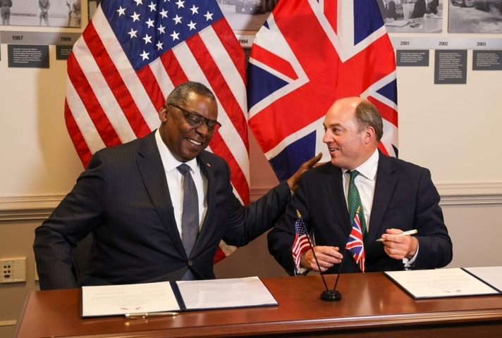 Ben Wallce and Lloyd Austin smile as they sign the agreement extension in front of the UK and US flags
