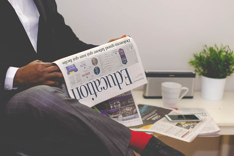 Man sitting, reading a newspaper