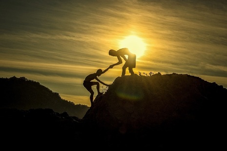 Silhouette of person helping companion climb on to a hilltop.