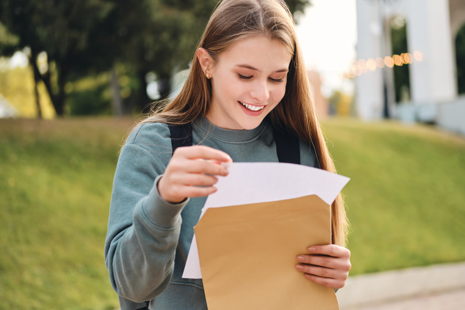 Female student opens envelope with results letter inside.