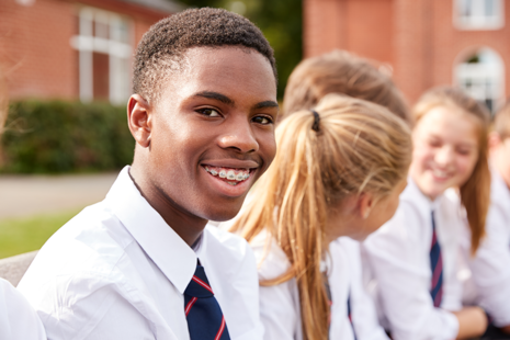 Male student smiles while sat with classmates.