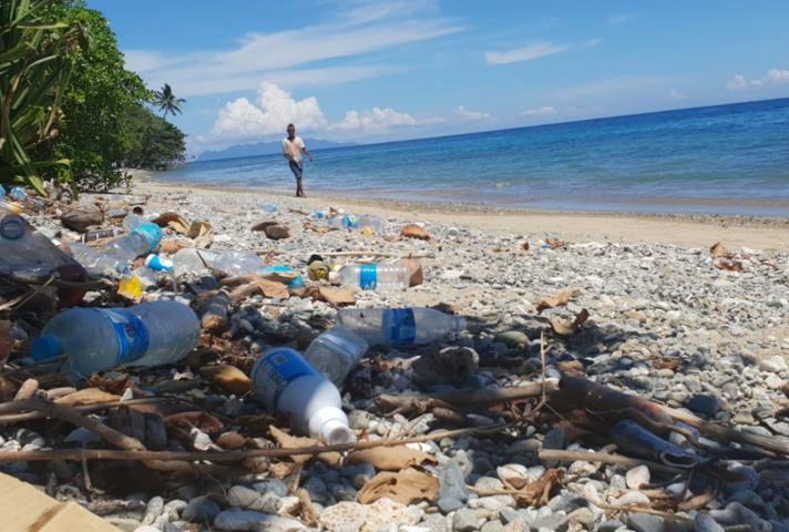 man walking on beach with litter