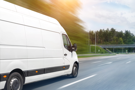 Photo of a white transit van driving on a road